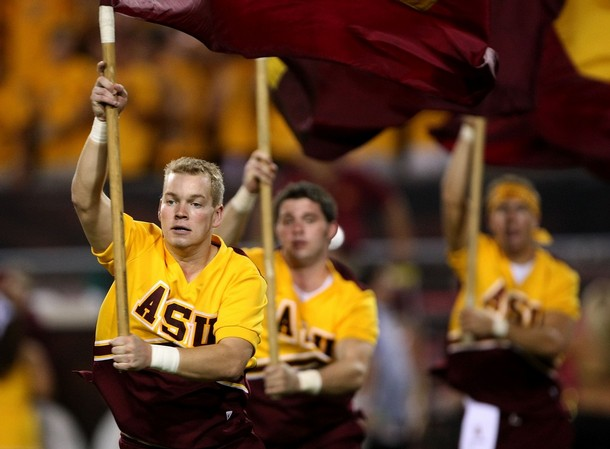 a picture of a few male cheerleaders running onto the football field with flags